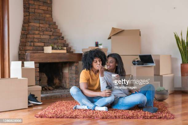 afro boyfriends eating ice cream in living room. - beige shoe stock pictures, royalty-free photos & images