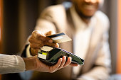 Afro businessman giving credit card to barman