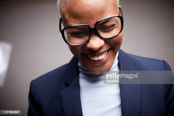 afro caribbean woman, dressed in a suit and wearing glasses, smiling and shy. - horn rimmed glasses stock pictures, royalty-free photos & images
