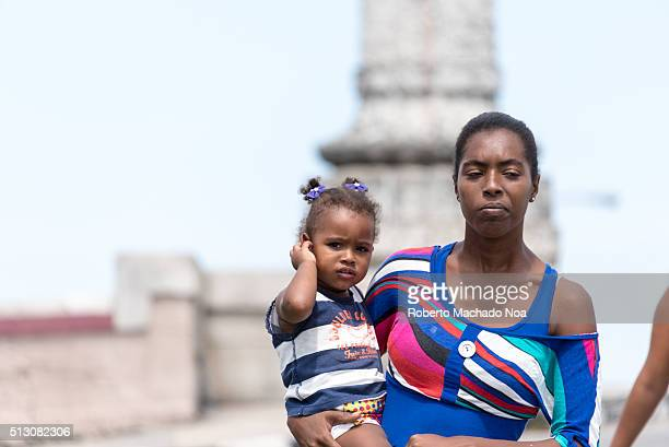 Afro Caribbean young single mother carrying her young daughter in her arms as she walks down the street on a sunny and hot day