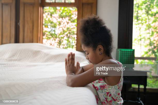 afro child praying at home - little girl giving head stock photos and pictures