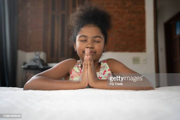 afro child praying at home - giving a girl head stock photos and pictures