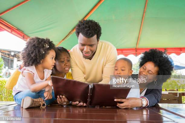 afro colombian family selects from the menu what to order to eat in a typical colombian restaurant called fonda - valle del cauca stock pictures, royalty-free photos & images