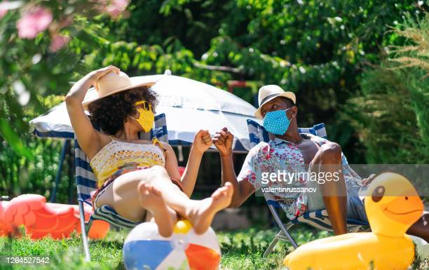 casal afro usando máscara facial protetora tendo staycation divertido no quintal e praticando saudação alternativa, durante covid-19 - summer - fotografias e filmes do acervo