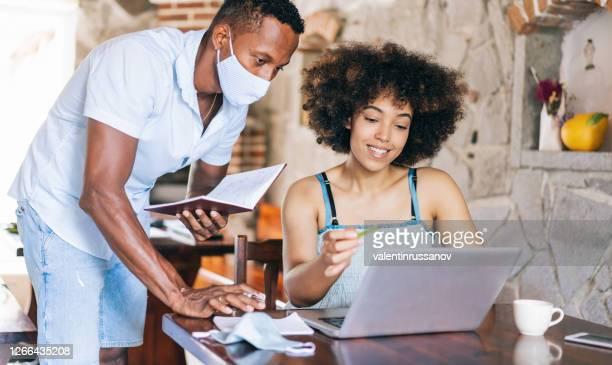 afro paar dat van huis, tijdens tijd in isolatie werkt en beschermend gezichtsmasker draagt, tijdens covid-19 - afro amerikaanse etniciteit stockfoto's en -beelden