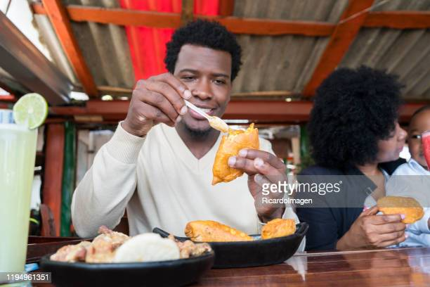afro dad happily eat a delicious cake and apply it spicy while preparing your bite - empanada stock pictures, royalty-free photos & images