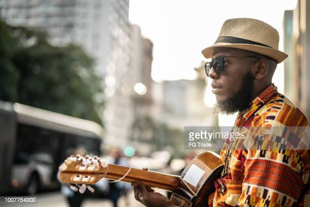 afro descent hipster man with guitar outdoor - reggae stock photos and pictures