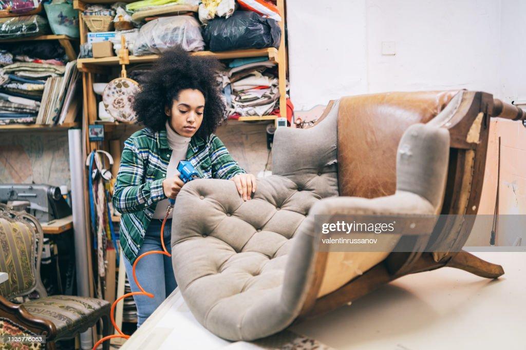 Afro Female Refurbishing Chair In Upholstery Workshop : Stock Photo