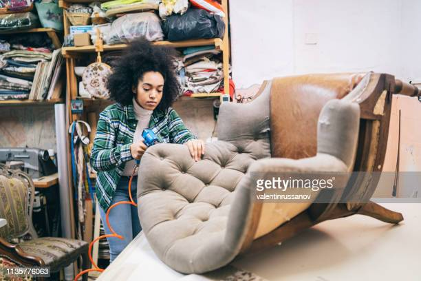 Afro Female Refurbishing Chair In Upholstery Workshop