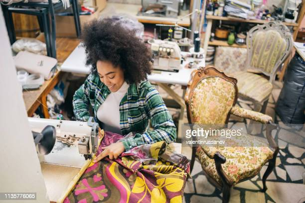 Afro Female mit Nähmaschine in der Upholsterwerkstatt