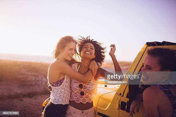 Afro girl and friend laughing on road trip at beach