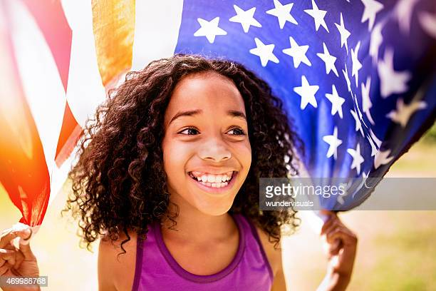 afro girl happily holding an american flag - fourth of july stock photos and pictures