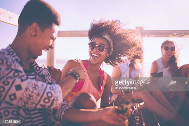 Afro girl in sunglasses laughing out loud with friends