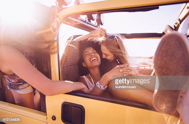 Afro girl laughing with friends on a road trip