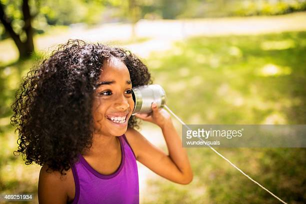 Afro girl listening to a tin can phone in park
