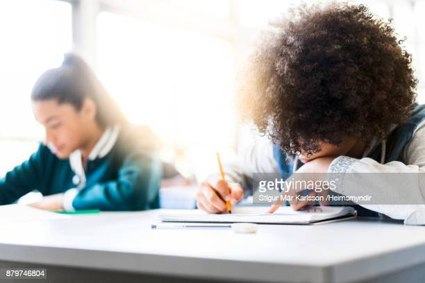 Afro girl writing in book by friend at school