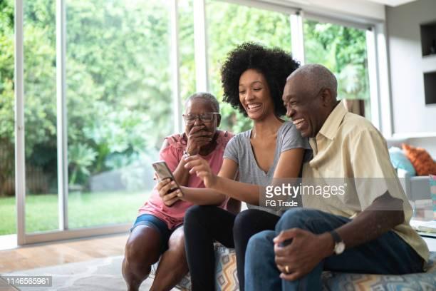 neta afro que mostra fotos em seu telemóvel a seus grandparents, povos que sorriem e que têm o divertimento - neto - fotografias e filmes do acervo