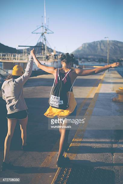 Afro grunge girl walking a yellow line at a harbour