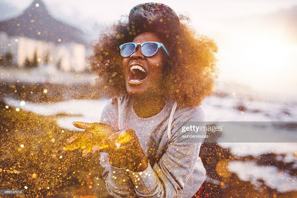 Afro hipster girl laughing ecstatically while throwing gold glitter : Stock Photo