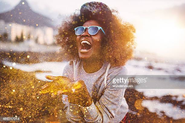 Afro hipster girl laughing ecstatically y tirando de oro brillante
