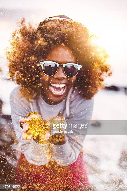 Afro hipster teen laughing as she is throwing gold glitter