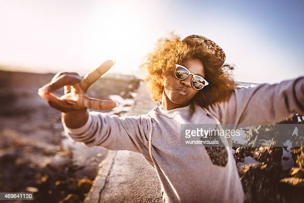 Afro hipster teen showing peace sign while at the beach