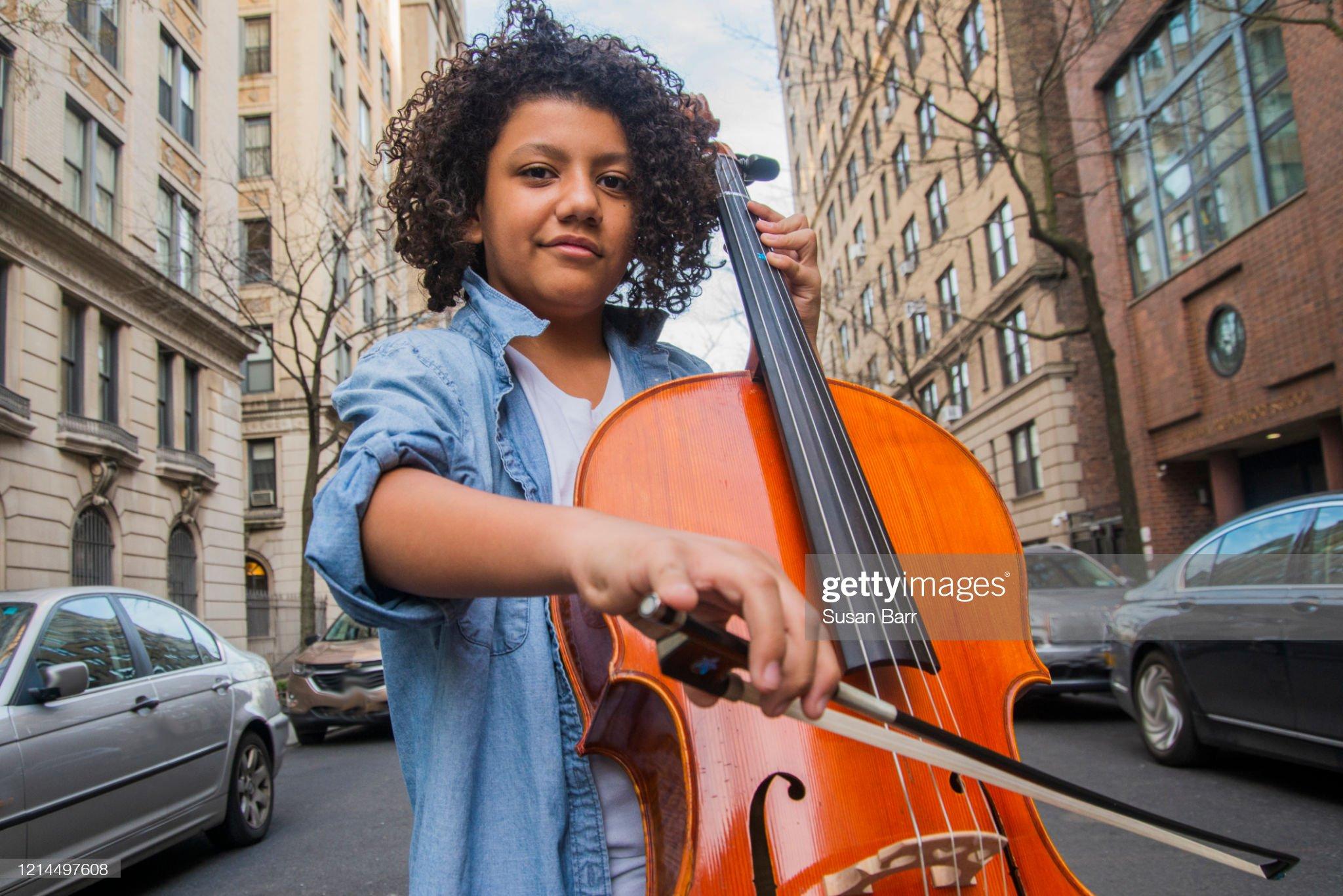 Afro Hispanic boy playing cello : Stock Photo