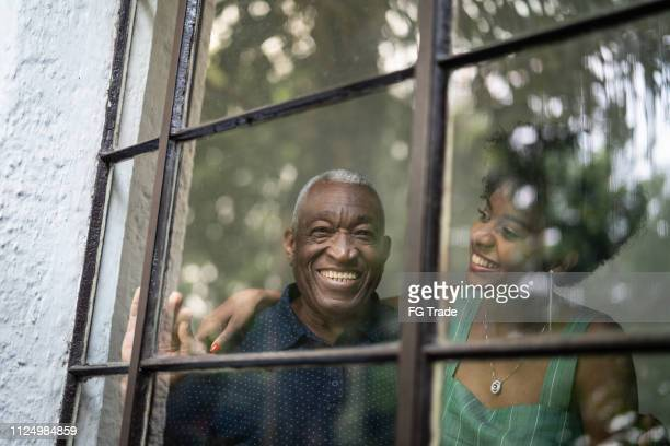afro hispanic latino grandfather and granddaughter embracing through the window - happy fathers day stock pictures, royalty-free photos & images