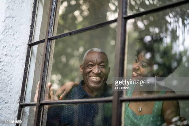 abuelo de latino hispano afro y nieta abrazando a través de la ventana - pareja hombre mayor y mujer joven fotografías e imágenes de stock
