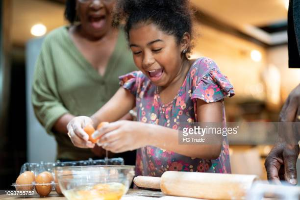 afro hispanic-latino grandparents teaching her granddaughter how to cook - pardo brazilian stock pictures, royalty-free photos & images