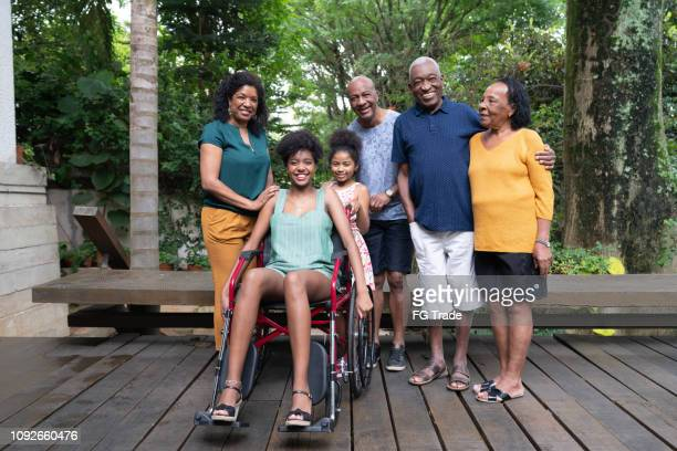afro hispanic-latino multi-generation family, and one of them on wheelchair portrait - african american man helping elderly stock pictures, royalty-free photos & images