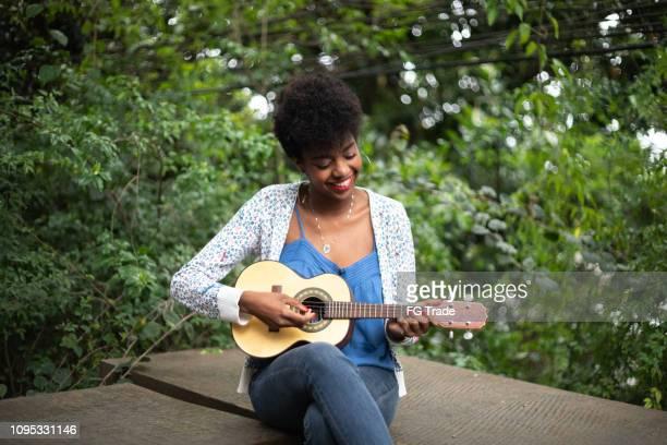 afro latino-hispânica jovem mulher tocando guitarra - músico - fotografias e filmes do acervo