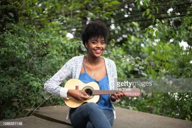 afro hispanic-latino young woman playing guitar - samba stock pictures, royalty-free photos & images