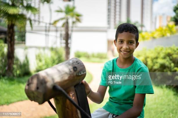 afro latino bambino ritratto cavallo da equitazione - solo bambini foto e immagini stock