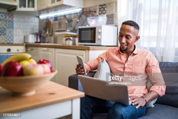 afro latinos trabalhando em um laptop e usando telefone inteligente em casa - escolher - fotografias e filmes do acervo