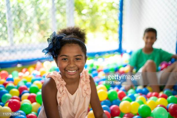 afro latinx children playing in plastic pool full colourful balls - portrait - kids pool games stock pictures, royalty-free photos & images