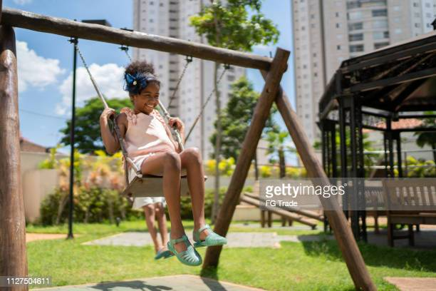 afro latinx children swinging in the playground - leisure activity stock pictures, royalty-free photos & images
