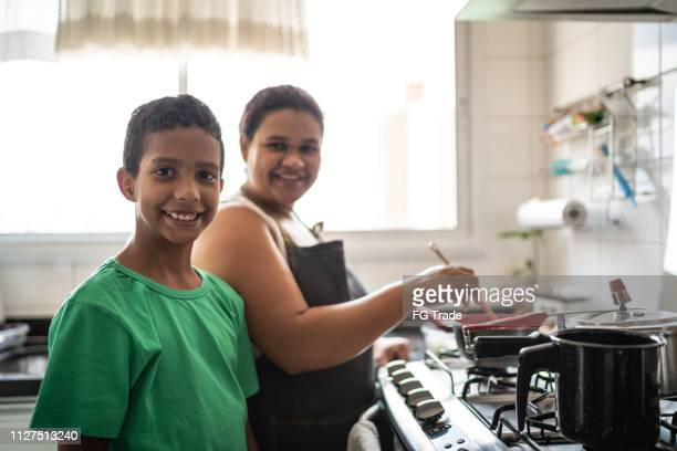 afro latinx mother and son cooking at home portrait - iberian ethnicity stock pictures, royalty-free photos & images