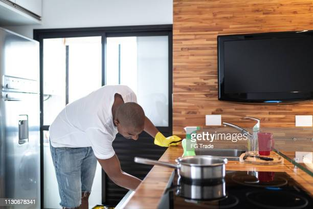 Afro man washing dishes at home