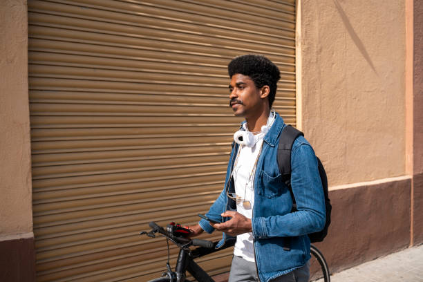Afro man with bicycle holding smart phone by wall during sunny day