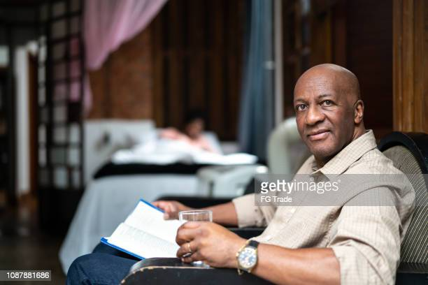 afro mature man reading a book at home - afro caribbean ethnicity stock pictures, royalty-free photos & images
