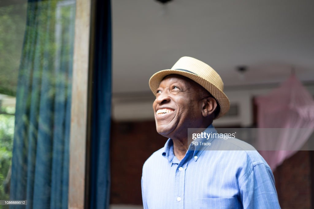 Afro Senior Looking Through The Window : Stock Photo