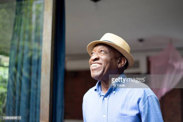 afro senior looking through the window - speranza foto e immagini stock