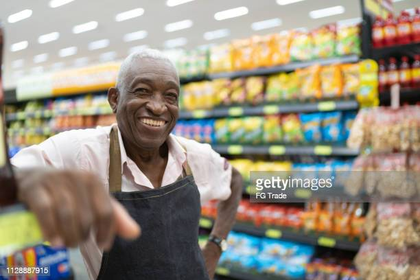 afro senior man business owner / employee at supermarket - happy merchant stock pictures, royalty-free photos & images