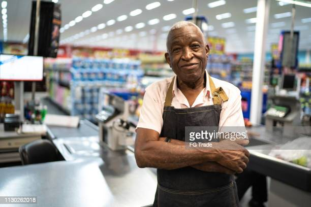 afro senior man business owner / employee at supermarket - assistant stock pictures, royalty-free photos & images