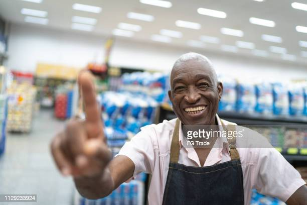 afro senior man business owner / employee at supermarket showing number one - number 1 stock pictures, royalty-free photos & images