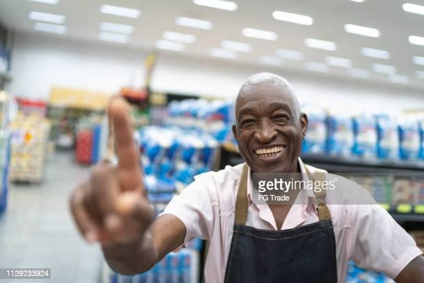 proprietário da empresa afro homem sênior / empregado de supermercado mostrando número um - medalha de ouro - fotografias e filmes do acervo