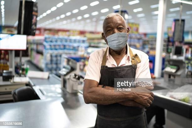 afro senior mann geschäftsinhaber / angestellter mit gesichtsmaske im supermarkt - essenzielle berufe und dienstleistungen stock-fotos und bilder