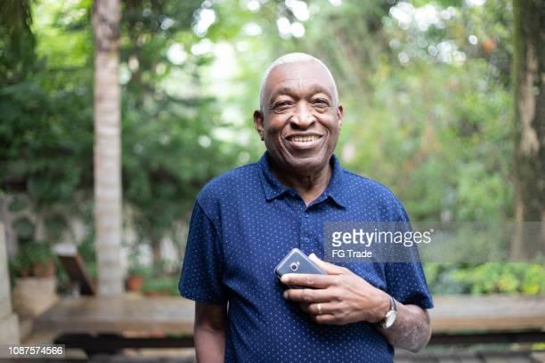 afro senior man using his mobile phone portrait - pardo brazilian stock pictures, royalty-free photos & images