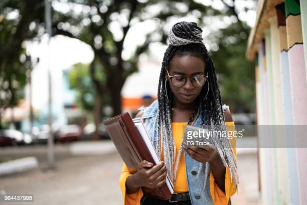 afro student/teacher on the move with mobile - brazilian girls stock photos and pictures